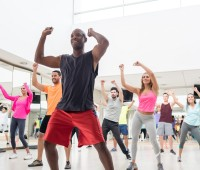 Diverse group of people at a rumba lesson in the gym all looking very happy and smiling