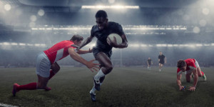 A mid action image of a professional black male rugby player running whilst holding a rugby ball and running pushing away a rival player who is about to tackle. The athlete has mouth open and teeth bared in determination. The action occurs in a generic misty floodlit rugby stadium.